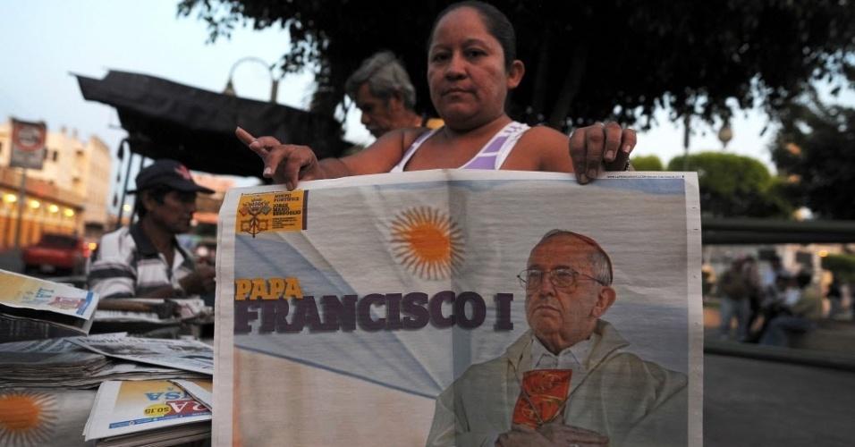 14.mar.2013 - Mulher vende jornal no centro de San Salvador com um especial sobre o papa Francisco, nesta quinta-feira (14). O argentino Jorge Mario Bergoglio foi eleito pelos cardeais no segundo dia do conclave