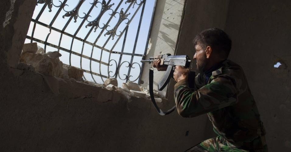 14.mar.2013 - Rebelde mira em tropas do regime de dentro de construção no aeroporto militar de Menagh, próximo a Aleppo, na Síria