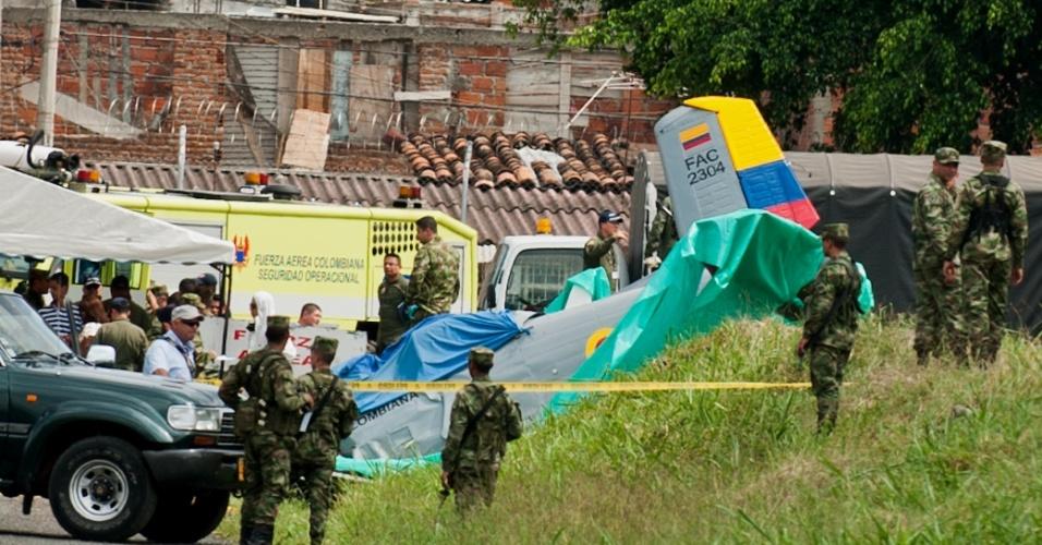 14.mar.2013 - Soldados cercam o avião militar de treinamento da Força Aérea da Colômbia que caiu nesta quinta-feira (14) em Cali (Colômbia). O instrutor e o aluno, ambos militares, morreram no acidente