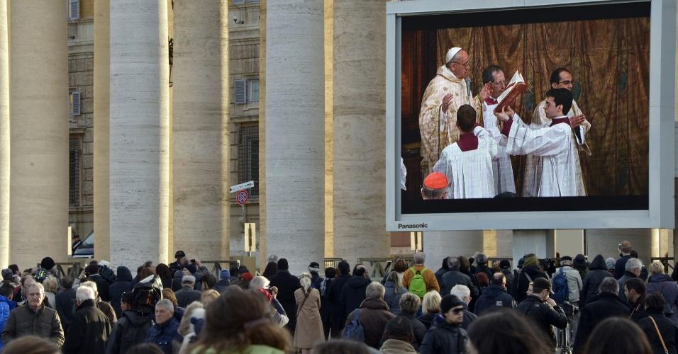 14.mar.2013 - Telão na praça São Pedro, no Vaticano, exibe a primeira missa do papa Francisco, celebrada na Capela Sistina