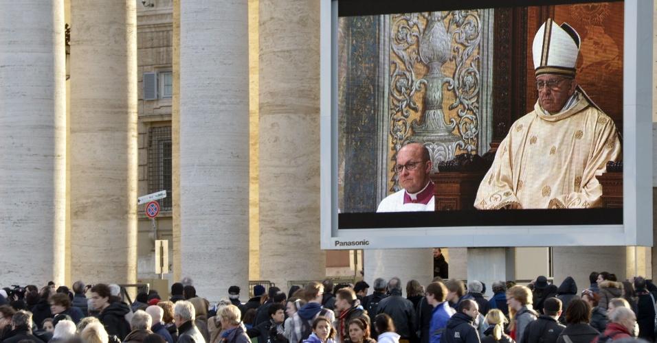14.mar.2013 - Telão na praça São Pedro, no Vaticano, exibe a primeira missa do papa Francisco, celebrada na Capela Sistina, nesta quinta-feira (14)
