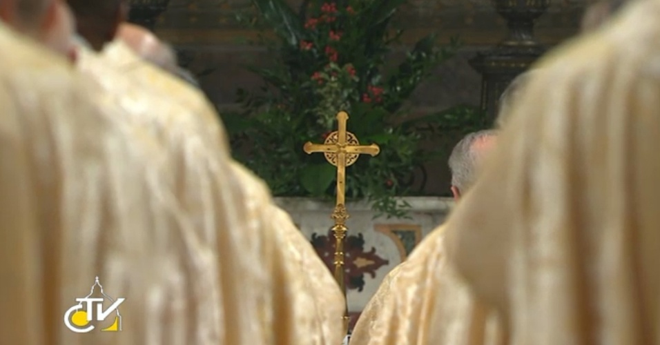 14.mar.2013 - Transmissão de TV mostra a cruz no altar da Capela Sistina, no Vaticano, entre os ombros dos cardeais que assistem à primeira missa do papa Francisco, celebrada nesta quinta-feira (14)
