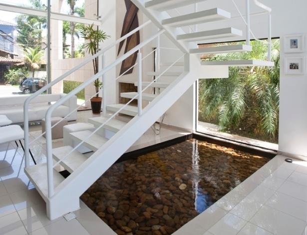 A viga central da escada é um tubo metálico que foi recheada com concreto, para evitar vibrações, e como os degraus são fôrmas metálicas preenchidas por cimento queimado branco, não fazem barulho. A escada leva pintura automotiva e cobre um espelho d'água com fundo de seixos. A arquitetura e os interiores são de autoria do arquiteto Flavio Castro