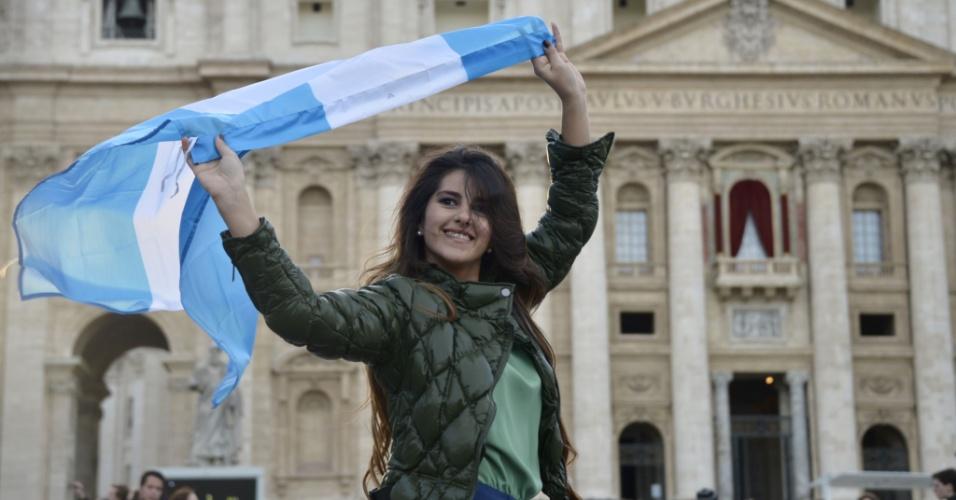 Mulher posa com a bandeira da Argentina em frente à basílica de São Pedro, na praça de mesmo nome, no Vaticano, nesta quinta-feira (14)
