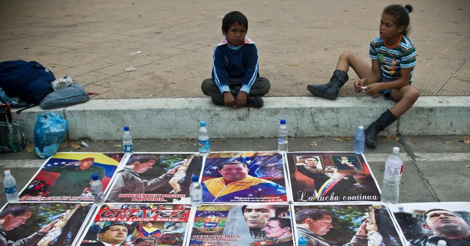 14.mar.2013 - Crianças vendem fotografias de Hugo Chávez em Caracas, na Venezuela. O corpo do líder, que faleceu aos 58 anos, será levado para museu militar na madrugada desta sexta-feira (15)