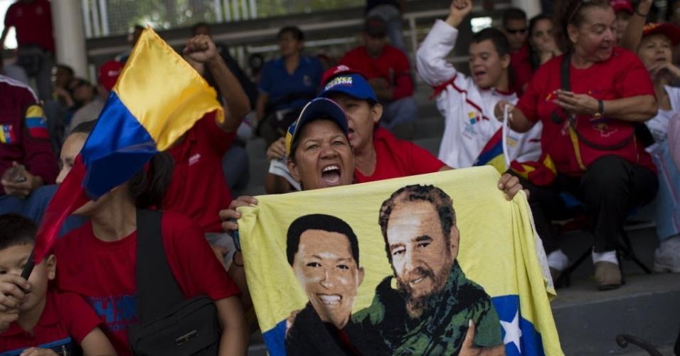 15.mar.20123 - Mulher mostra bandeira com imagem do venezuelano Hugo Chávez abraçando o cubano Fidel Castro na arquibancada montada no Paseo de Los Próceres, em Caracas, na Veneuela. Cortejo com o caixão de Chávez até um museu militar vai percorrer mais de 18 quilômetros na capital venezuelana