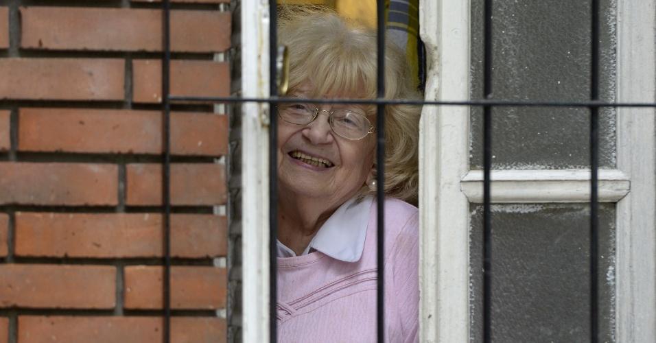 """15.mar.2013 - A argentina Amalia Damonte, que foi namorada de Jorge Bergoglio -- agora nomeado papa Francisco -- há mais de 60 anos, surge na janela de sua residência no bairro de Flores, em Buenos Aires, nesta sexta-feira. Na época, Bergoglio teria dito a ela """"Se você não se casar comigo, me tornarei padre"""", segundo Damonte"""