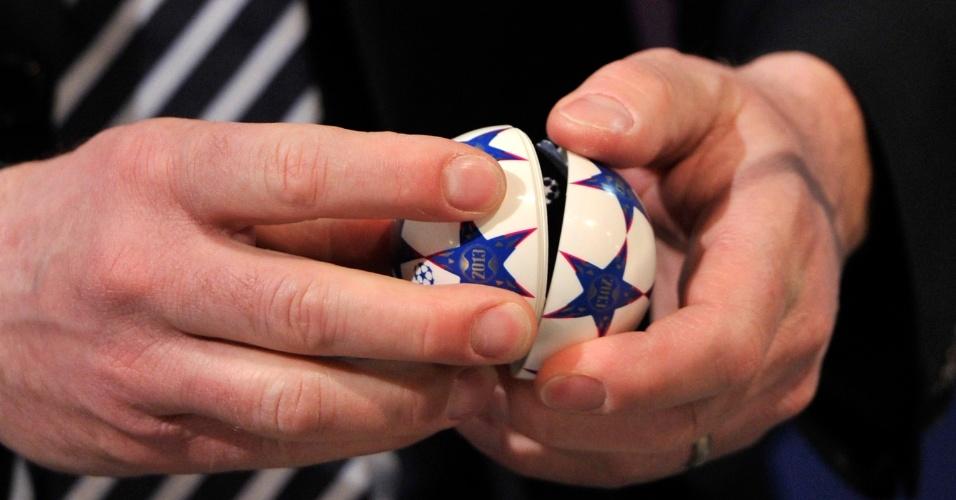 15.mar.2013 - Bolinha com nome de equipe é aberta durante o sorteio das quartas da Liga dos Campeões