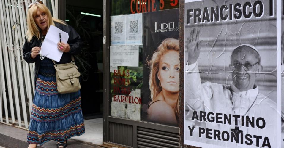 15.mar.2013 - Mulher observa cartaz com a foto do papa argentino no qual está escrito ?Francisco 1º - Argentino e Peronista?, em rua de Buenos Aires, nesta sexta-feira