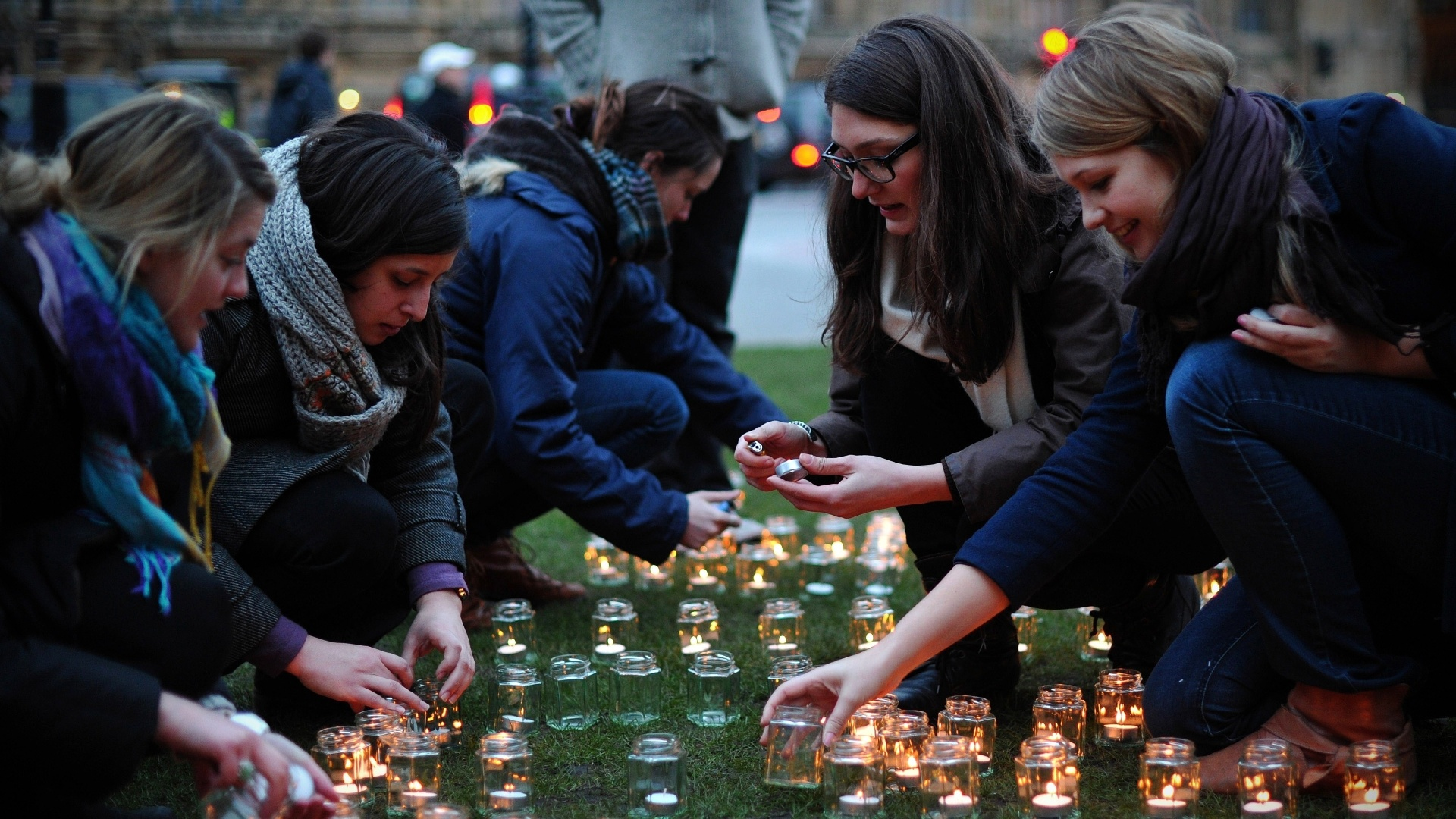 15.mar.2013 - Mulheres acendem velas no centro de Londres, no Reino Unido, em ao mundial da ONG Save the Children na noite desta quinta-feira (14).  A vgilia, que ocorreu em 20 cidades diferentes, lembra os dois anos de levante popular contra o regime de Bashar Al-Assad
