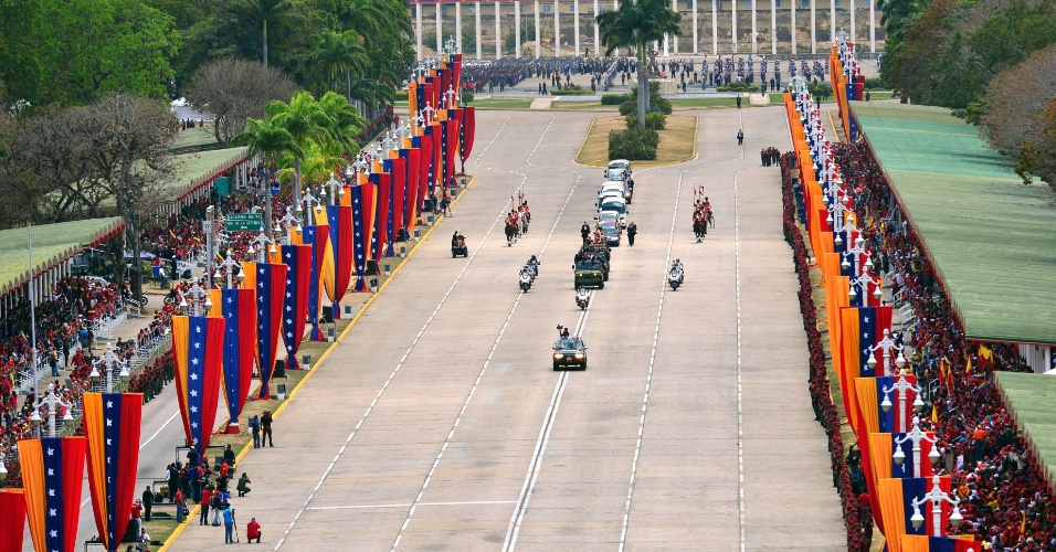 15.mar.2013 - O caixão com o corpo do presidente Hugo Chávez é transportado por um carro fúnebre, na manhã desta sexta-feira (15), em Caracas, da Academia Militar, onde era velado desde 6 de março, até o Museu Histório Militar, também chamado de Quartel da Montanha. O translado recebeu honras militares, e carro com o caixão é escoltado por membros da cavalaria