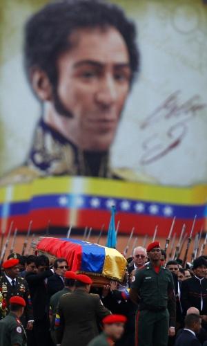 """15.mar.2013 - O caixão com o corpo do presidente Hugo Chávez, morto em 5 de março, é carregado durante o translado que o transportou da Academia Militar de Caracas até o Museu Histórico Militar, onde o governo da Venezuela anunciou a intenção de embalsamá-lo para ficar exposto ao público. Ao fundo, um mural estampa o rosto de Simón Bolívar, herói da independência venezuelana e ídolo de Chávez, que batizou em sua homenagem o movimento político do """"bolivarianismo"""""""
