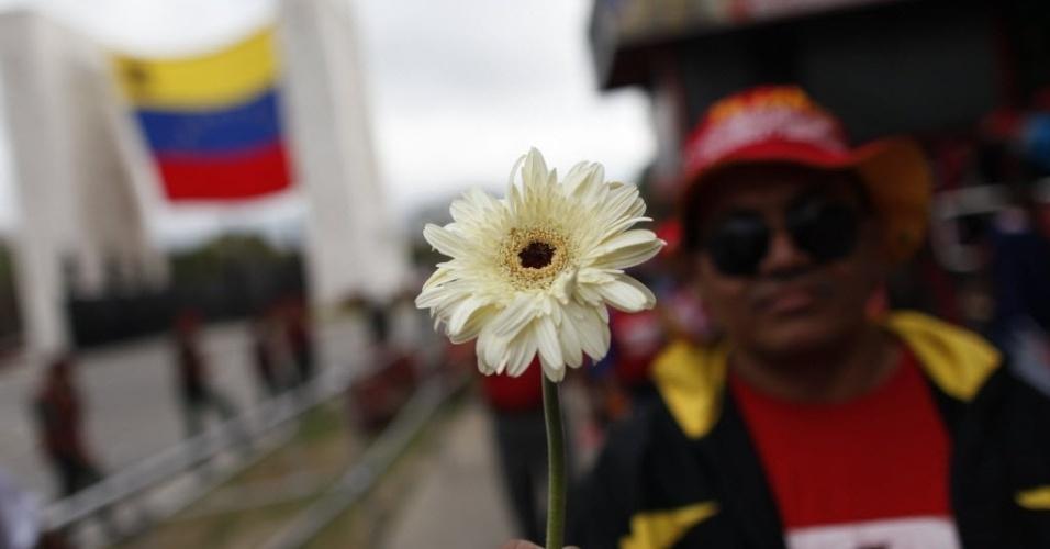 15.mar.2013 - Simpatizante de Hugo Chávez aguarda no Paseo de Los Próceres, em Caracas, na Veneuela, para ver a transferência do caixão do líder morto no último dia 5 - o cortejo até um museu militar vai percorrer mais de 18 quilômetros na capital venezuelana