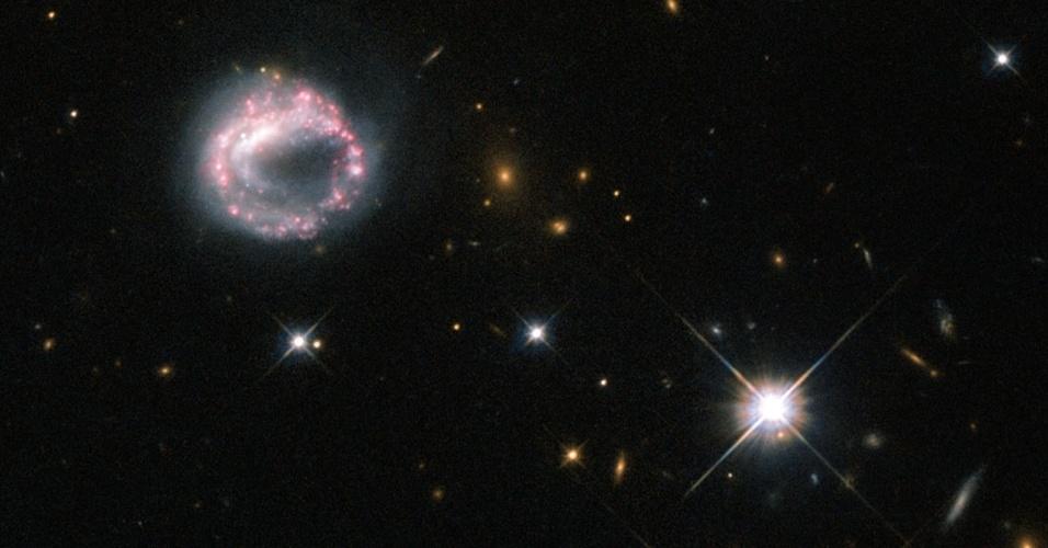 15.mar.2013 - Telescópio Hubble captura imagem de galáxia em formato de anel, a Zw II 28, que intriga os astrônomos. Acredita-se que elas se formam quando uma galáxia passa pelo disco de outra galáxia maior -- como as galáxias têm muitos espaços vazios, a colisão não é destrutiva, mas a gravidade causa efeitos, gerando um grande centro denso, circulado por estrelas brilhantes. A Zw II 28 com um círculo rosa e roxo não é uma galáxia em anel típica porque não tem uma galáxia par visível. Mas agora os astrônomos descobriram que ela pode ter um companheiro que estaria dentro do círculo