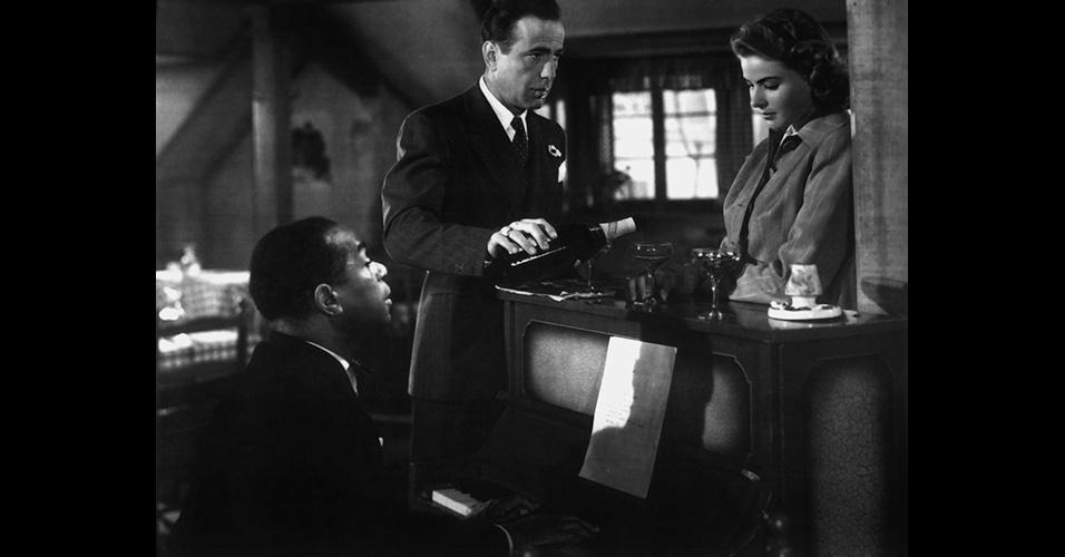"""Humphrey Bogart fazia sucesso nos anos 1930 e 1940, e foi eternizado no clássico """"Casablanca"""" (1942). Tudo bem que a imagem mais emblemática seja a com o trench coat, mas no filme aparece também o smoking branco conhecido por """"summer jacket"""" (de paletó de verão, em inglês) e o terno risca-de-giz combinado com gravata de bolinha, que pode ser usado desta maneira até hoje"""