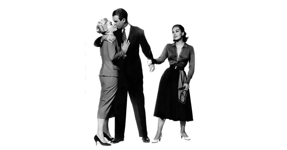 """Nos anos 1950, a silhueta ficou mais relaxada e os paletós não marcavam tanto a cintura, os colarinhos diminuíram e, por conseguinte, as gravatas ficaram mais estreitas. As calças continuam folgadas, com pregas, e barra italiana, como podemos ver em James Stewart em """"Um corpo que cai"""" (1958)"""