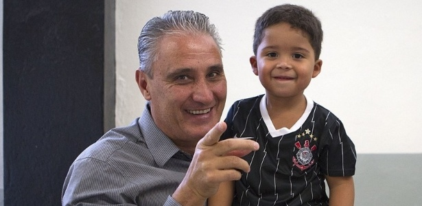 16.03.2013 - Tite, tcnico do Corinthians, tira foto com o filho de Jorge Henrique, que acompanhou o Corinthians no vestirio, antes do jogo com a Unio Barbarense