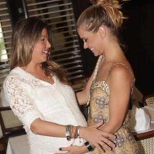 16.mar.2013 - Carolina Dieckmann (à dir) coloca a mão na barriga da mulher de Marcelo Serrado, Roberta durante a premiação