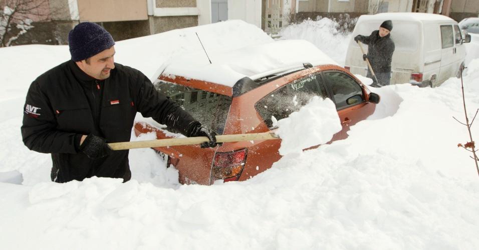 16.mar.2013 - Homem tira grossa camada de neve que atingiu carros no centro de Minsk após tempestade na capital bielorrussa