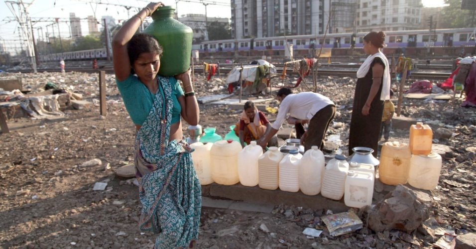 16.mar.2013 - Indianos que vivem em favelas perto dos trilhos de ferrovia enchem vasos com água em torneira pública em Mumbai, na Índia, neste sábado (16). A população depende das torneiras públicas, visto que não há fornecimento direto de água na maioria das favelas