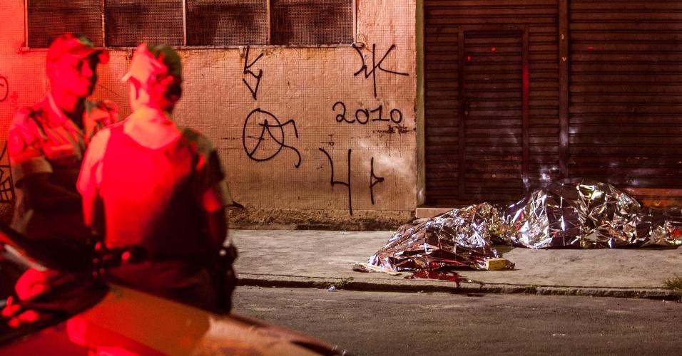 16.mar.2013 - Policiais observam corpo de dois homens que foram baleados no bairro do Belém, zona leste de São Paulo