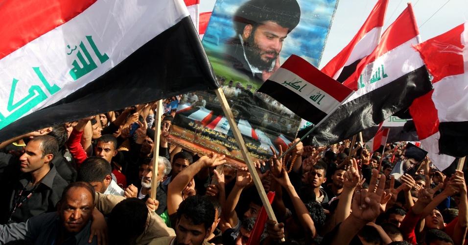 16.mar.2013 - Seguidores do clérigo iraquiano xiita Moqtada al-Sadr agitam bandeiras nacionais em Bagdá por ocasião dos dez anos da invasão norte-americana no país