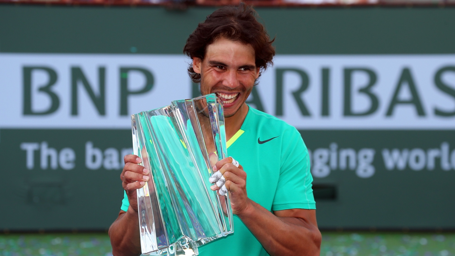 17.mar.2013 - Nadal moder o troféu conquistado em Indian Wells