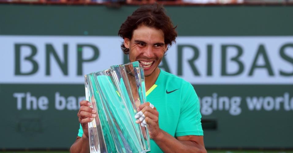 17.mar.2013 - Nadal moder o troféu conquistado em Indian Wells