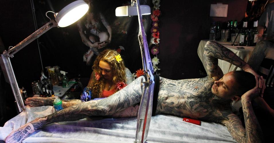 17.mar.2013 - Tatuador trabalha na perna de um cliente no Festival de Body Art em Tel Aviv (Israel)
