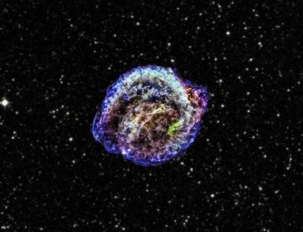 18.mar.2013 - A remanescente da supernova de Kepler, descoberta em 1604, é resultado de uma explosão termonuclear da interação de duas estrelas, uma anã-branca e uma gigante vermelha, segundo estudo da Universidade do Estado da Carolina do Norte, nos Estados Unidos. Com dados do observatório de raios x Chandra, da Nasa (Agência Espacial Norte-Americana), astrônomos identificaram magnésio (elemento que não é encontrado em supernovas e que pode ter sido sugado da gigante pela anã-branca) em um disco no centro da remanescente, cujo formato é moldado geralmente por ventos soprados por uma estrela, e não por material expelido por supernovas
