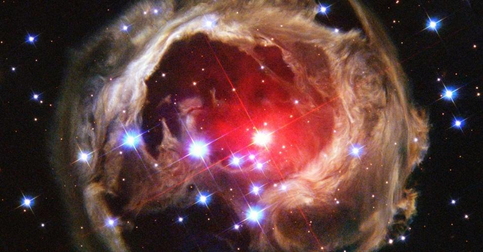 18.mar.2013 - A estrela V838 Mon, que fica a 20 mil anos-luz na Constelação do Unicórnio, ainda enfrenta um eco de luz, fenômeno em que o brilho refletido por um meio chega ao observador depois do flash inicial (que pode ser causado pela explosão de uma supernova, por exemplo), como mostra imagem acima do telescópio espacial Hubble. Segundo a Nasa (Agência Espacial Norte-Americana), isso acontece porque a luz continua a ser refletida pelos anéis de poeira cada vez mais distantes que cercam a estrela, o que já abrange um diâmetro de 6 anos-luz
