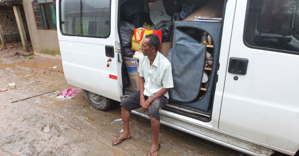 18.mar.2013 - Aposentado Antonio Jurandir, 48, observa área alagada da comunidade de Pilão, Cubatão (SP), após colocar os móveis em sua van. Casas do bairro foram inundadas pela segunda vez em menos de 30 dias