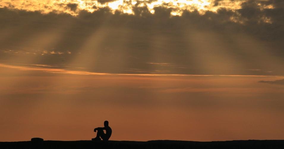 18.mar.2013 - Homem senta ao pôr do sol na avenida costeira El Malecon, em Havana (Cuba)