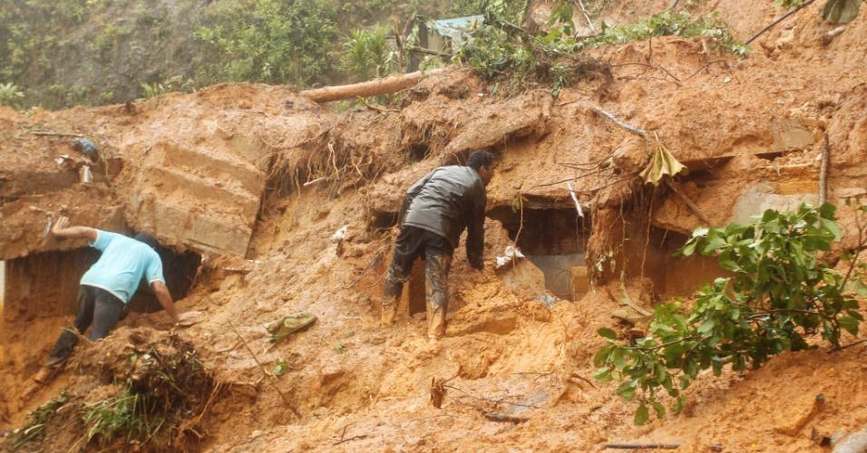 18.mar.2013 - Moradores do bairro Independência, em Petrópolis (RJ), procuram sobreviventes do deslizamento que soterrou uma família