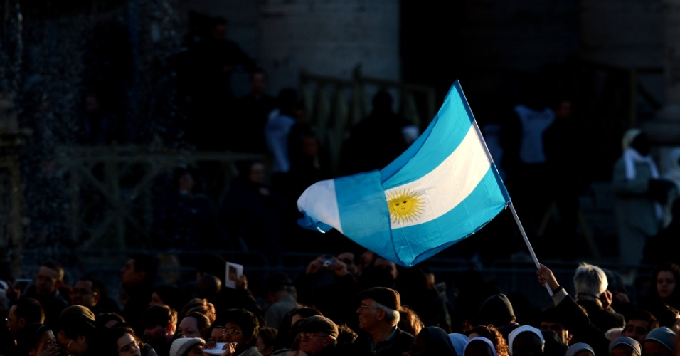19.mar.2013 - Bandeira argentina é agitada na praça de São Pedro, no Vaticano, antes da missa inaugural do papa Francisco. O novo papa recebe, oficialmente, os símbolos do seu pontificado, como o anel de pescador