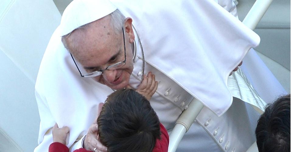 19.mar.2013 - O papa Francisco abençoa a uma criança durante travessia da praça de São Pedro, no papamóvel aberto, para a missa inaugural de seu pontificado. Milhares de pessoas, de diversas nacionalidades, acompanham a missa diretamente do Vaticano