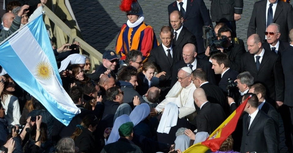 """19.mar.2013 - Papa Francisco (centro, de branco) cumprimenta fiéis ao chegar à praça de São Pedro, para sua missa inaugural no Vaticano. O Sumo Pontífice acenou aos presentes, que o saudaram aos gritos de """"vida longa ao papa"""""""