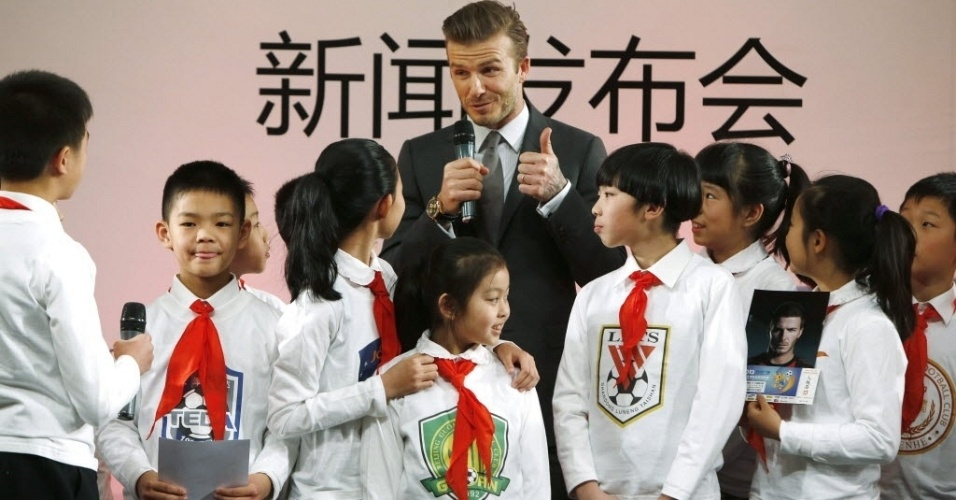 20.mar.2013 - David Beckham é cercado por crianças durante evento em Pequim