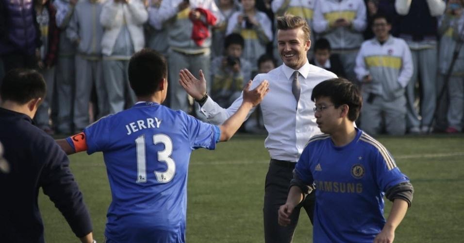 20.mar.2013 - David Beckham não perdeu a elegância no visual para jogar bola com crianças na China