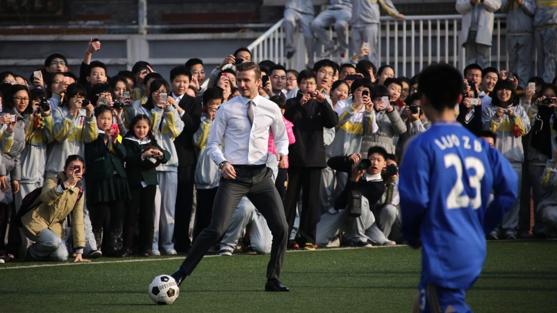 20.mar.2013 - David Beckham nem se importou com os trajes sociais e bateu bola com estudantes na China