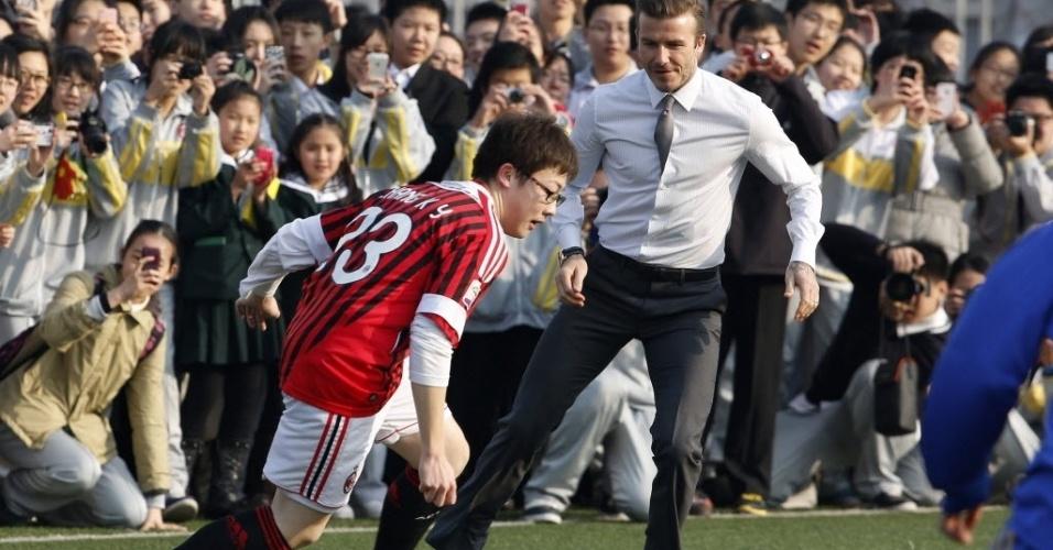 20.mar.2013 - Gravata e sapatos sociais não foram problema para David Beckham jogar bola com estudantes chineses