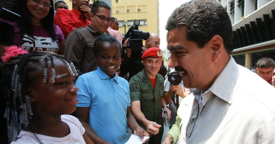 """20.mar.2013 - O presidente interino da Venezuela, e candidato chavista nas eleições presidenciais de 14 de abril, Nicolás Maduro, conversa com uma criança em ato de campanha próximo ao Teatro Municipal de Caracas. Maduro afirmou nesta quarta-feira (20) que a morte de Hugo Chávez foi um """"duro golpe"""" para o movimento político representado pelo líder venezuelano"""