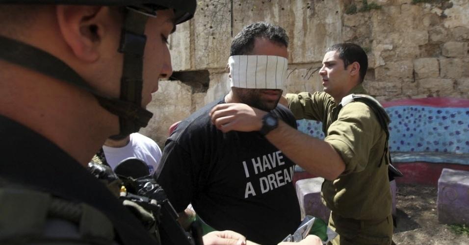 20.mar.2013 - Soldado israelense venda os olhos de manifestante palestino envolvido em protestos realizados em Hebron contra a visita do presidente dos EUA, Barack Obama, a Israel