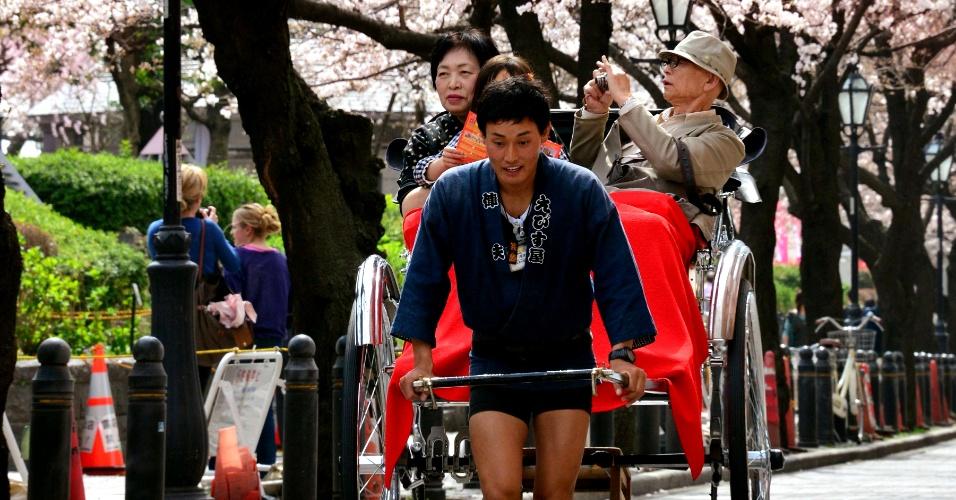 20.mar.2013 - Turistas são carregados em riquixá sob cerejeiras florescendo, ao longo de avenida beira-rio em Tóquio. A floração das cerejeiras marca o início da primavera no Japão e é um evento social, apreciado por milhões de pessoas