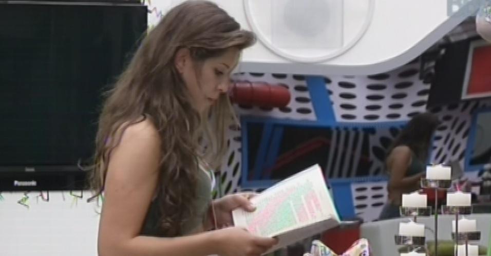 21.mar.2013 - Andressa lê livro na sala de estar após acordar