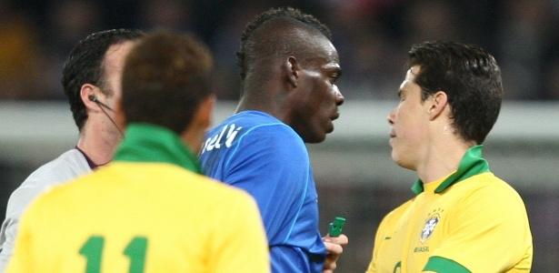 Atacante Balotelli (esq) e volante Hernanes discutem durante amistoso entre Brasil e Itália