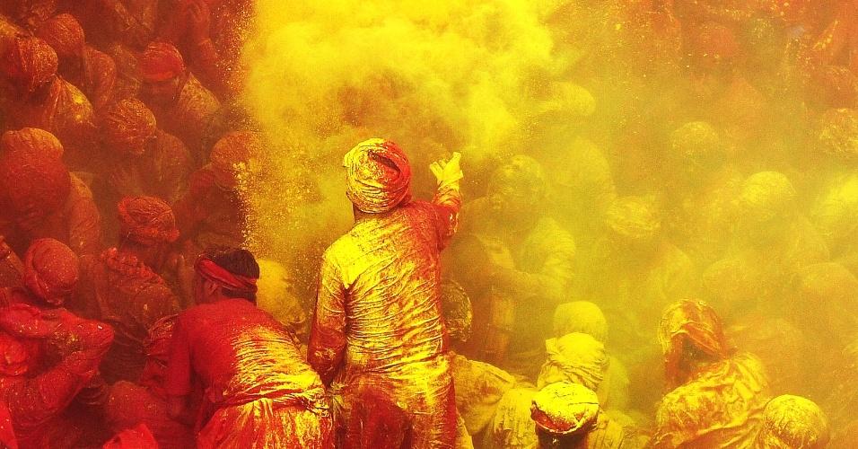 21.mar.2013 - Devotos hindus jogam pó colorido no Templo Radha Rani, em Barsana, na Índia, durante o Lahtmar Holi, o Festival das Cores indiano