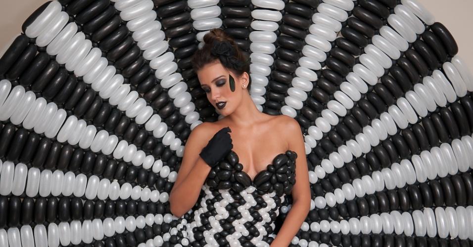 22.mar.2013 - Assistente de palco de Luciano Huck posa com vestido feito de balões