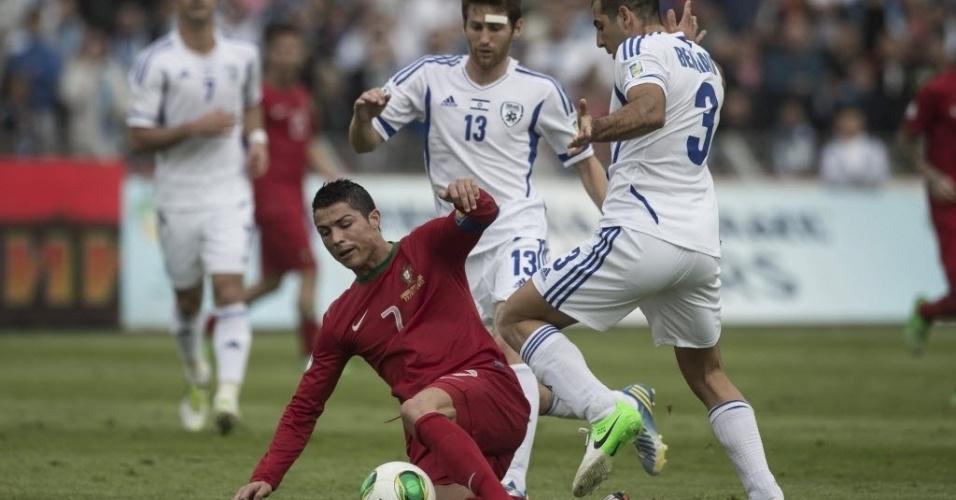 22.mar.2013 - Cristiano Ronaldo tenta jogada para Portugal cercado por dois jogadores de Israel em partida válida pelas eliminatórias europeias