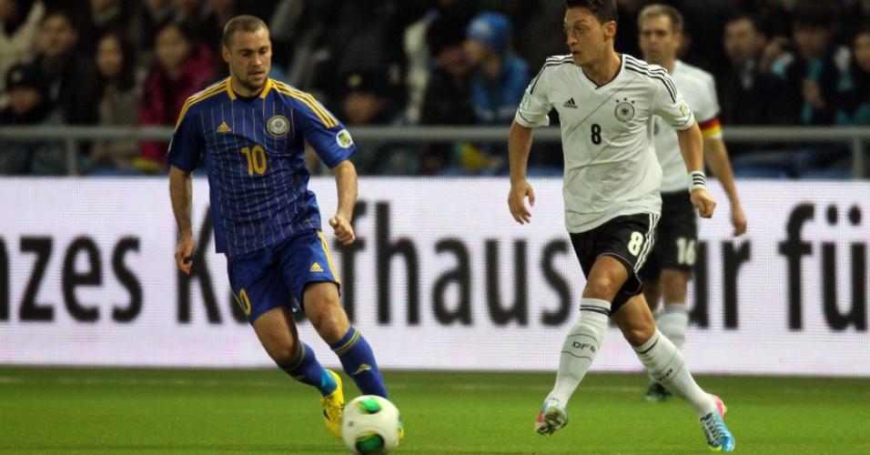 22.mar.2013 - Observado por Pavel Shabalin (esq), do Cazaquistão, meia Mesut Özil, da Alemanha, toca bola durante jogo das eliminatórias europeias